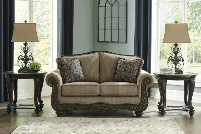 Διθέσιος καναπές Briaroaks, από την Ashley®. Με σκαλίσματα στον ξύλινο σκελετό και ταπετσαρία σε καφέ-ο-λε χρώμα και δύο διακοσμητικά μαξιλάρια.