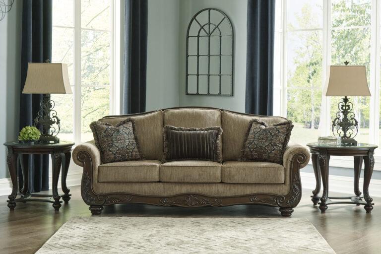 Τριθέσιος καναπές Briaroaks, από την Ashley®. Με σκαλίσματα στον ξύλινο σκελετό και ταπετσαρία σε καφέ-ο-λε χρώμα και τρία διακοσμητικά μαξιλάρια.