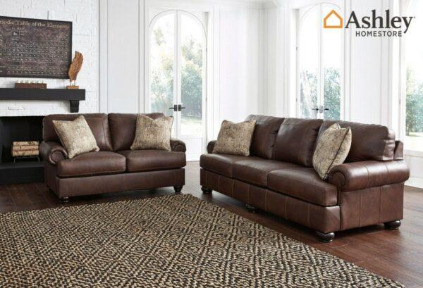 Τριθέσιος καναπές Beamerton, της Ashley®. Είναι επενδεδυμένος από γνήσιο δέρμα και διαθέτει αναπαυτικά μπράτσα, εμφανείς ραφές και εμφανή στρογγυλά πόδια.