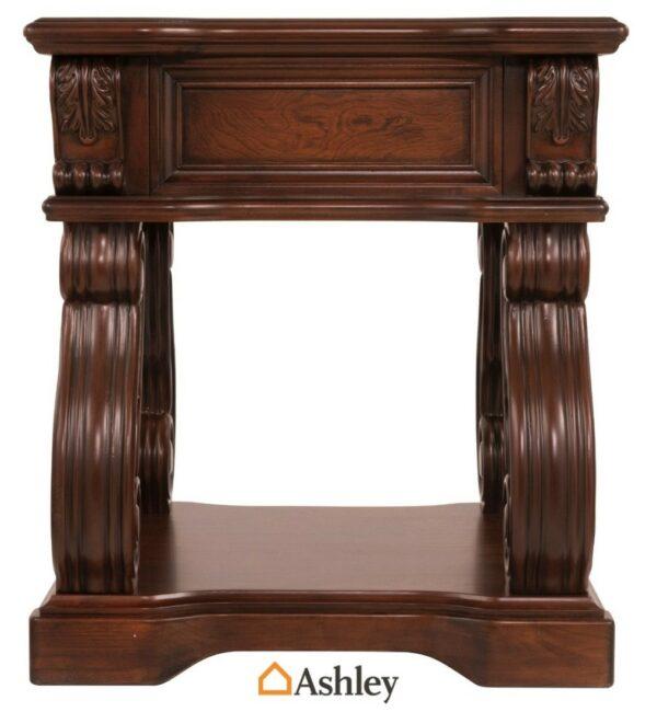 Βοηθητικό τραπεζάκι Alymere της Ashley, με κυρτά σκαλιστά πόδια, συρτάρι και ένα ράφι, στο κάτω τμήμα του.