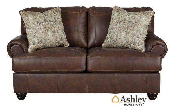 Διθέσιος καναπές Beamerton, της Ashley®. Είναι επενδεδυμένος από γνήσιο δέρμα και διαθέτει αναπαυτικά μπράτσα, εμφανείς ραφές και εμφανή στρογγυλά πόδια.