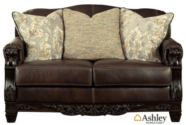 Διθέσιος καναπές Embrook της Ashley® από ξύλο και γνήσιο δέρμα. Με περίτεχνο σκάλισμα, αποσπώμενα μαξιλάρια καθίσματος και απαλά διακοσμητικά μαξιλάρια.