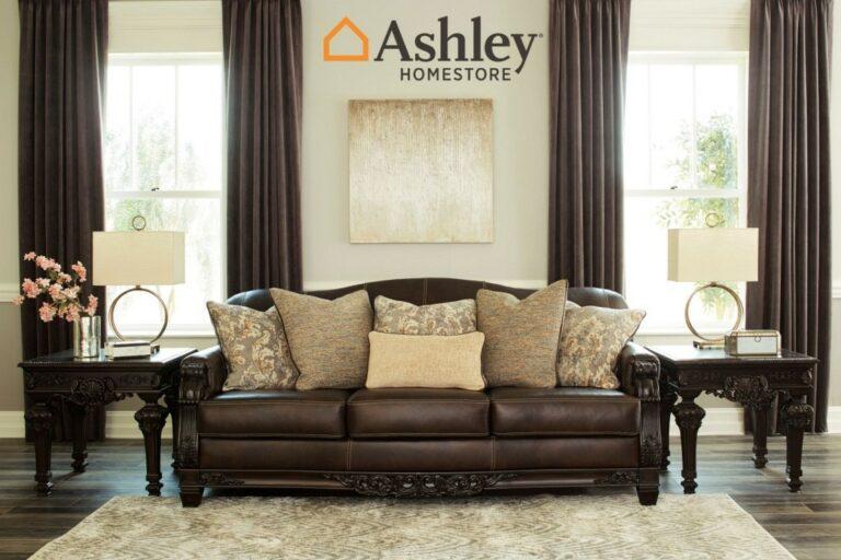 Τριθέσιος καναπές Embrook της Ashley® από ξύλο και γνήσιο δέρμα. Με περίτεχνο σκάλισμα, αποσπώμενα μαξιλάρια καθίσματος και απαλά διακοσμητικά μαξιλάρια.