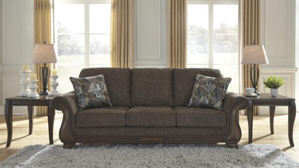 Τριθέσιος καναπές Miltonwood της Ashley με εμφανή τμήματα ξύλινου σκελετού και παχιά μαξιλάρια με ταπετσαρία σε χρώμα καφέ βελανιδιάς.