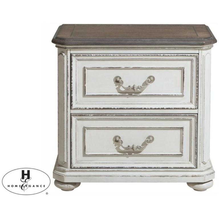 Κομοδίνο Willowick της Home Elegance. Είναι σε χρώμα λευκό αντικέ, με δύο συρτάρια με μηχανισμό και σκαλιστά μεταλλικά πόμολα.
