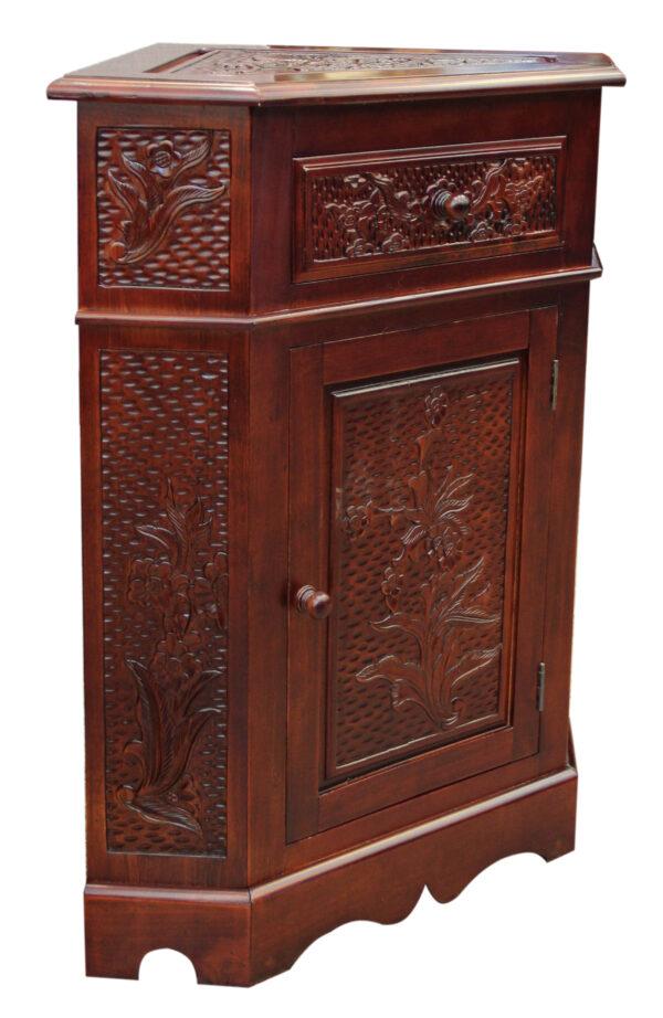 Γωνιακό ξύλινο ντουλάπι, σκαλισμένο σε όλες τις εμφανείς του επιφάνειες. Στο άνω τμήμα του διαθέτει ένα συρτάρι. Με βερνίκι σε σκούρα απόχρωση.